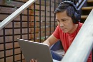 Man listening music through laptop computer while sitting on steps - CAVF41581