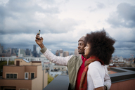 Couple taking selfie while standing on building terrace - CAVF41623