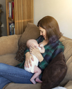 Woman breastfeeding daughter while sitting on sofa at home - CAVF41647