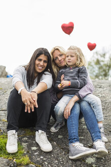 Portrait of happy female homosexual family relaxing on rock - MASF04679