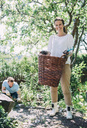 Portrait of happy woman carrying wicker basket with man gardening in background at yard - MASF04688
