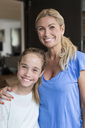 Portrait of happy girl standing with mother standing outside house - MASF04700