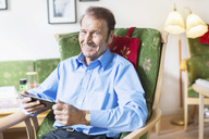 Portrait of happy senior man holding digital tablet while sitting on armchair at nursing home - MASF04709