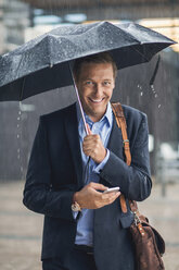 Portrait of smiling businessman using smart phone in city during rainy season - MASF04712