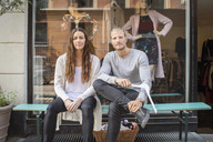 Portrait of owner with female worker sitting in front of clothing store - MASF04715