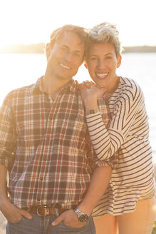 Portrait of loving couple standing on beach during sunset - MASF04718