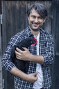 Portrait of happy man carrying hen at poultry farm - MASF04724