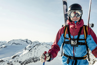 Portrait of smiling male skier standing on snowcapped mountain against clear sky - MASF04739