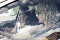 Senior women discussing over digital tablet in car - MASF04745