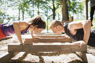 Side view of couple doing push-ups at outdoor gym - MASF04757