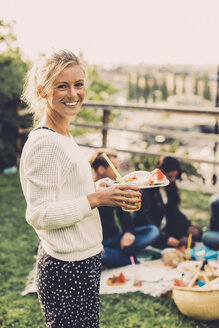 Side view portrait of happy woman holding breakfast at rooftop party - MASF04760