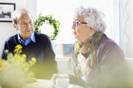Senior woman talking to friends at breakfast table in nursing home - MASF04763