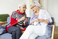 Senior women discussing while knitting at nursing home - MASF04766