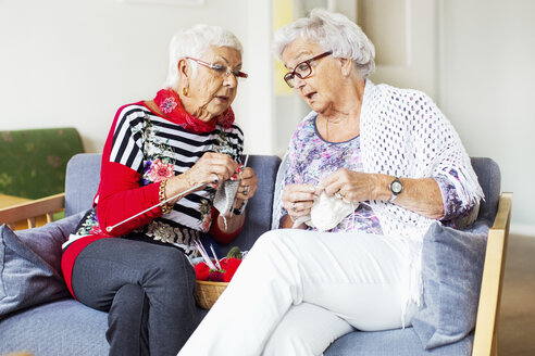 Senior women discussing while knitting at nursing home - MASF04766