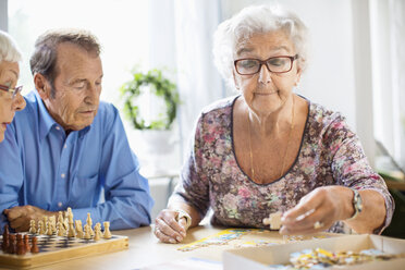 Senior people playing leisure games at table in nursing home - MASF04769