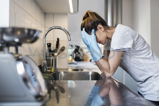Side view of tensed woman leaning at sink in kitchen - MASF04790