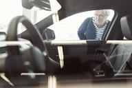 Senior woman admiring car displayed in store - MASF04796