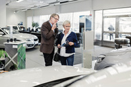 Senior couple discussing over car in store - MASF04799
