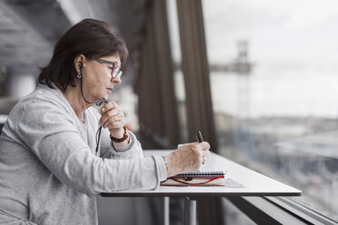 Side view of senior businesswoman using hands-free device by window in office - MASF04802