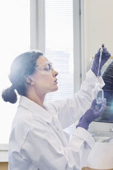 Side view of female scientist using pipette while examining chemical in laboratory - MASF04808
