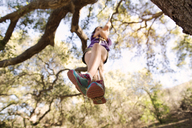 Low angle view of girl playing on rope swing in forest - CAVF41696