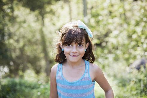 Portrait of cute girl smiling in forest - CAVF41705