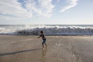 Full length of boy running from rushing waves at beach against sky - CAVF41738