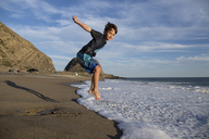 Portrait of boy jumping in surf at beach against sky - CAVF41744