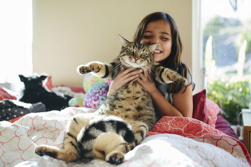 Happy girl with cat sitting on bed at home - CAVF41756