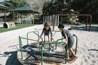 Siblings playing on carousel in playground - CAVF41765