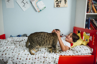 Boy playing with cat while lying on bed at home - CAVF41768