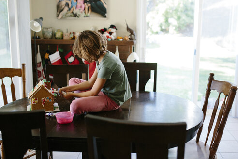 Girl making gingerbread house on table at home - CAVF41783
