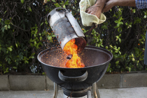 Cropped hands of man putting coals in barbecue at backyard - CAVF41786