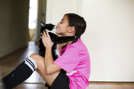 Playful girl kissing cat while sitting on floor at home - CAVF41798