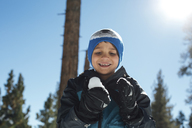 Low angle view of happy boy playing with snow against blue sky in forest - CAVF41804