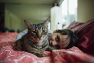 Portrait of cat by boy on bed at home - CAVF41813