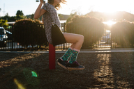 Side view of girl swinging at playground - CAVF41825