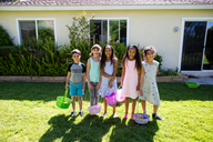 Portrait of happy friends and siblings holding Easter baskets at yard during sunny day - CAVF41831