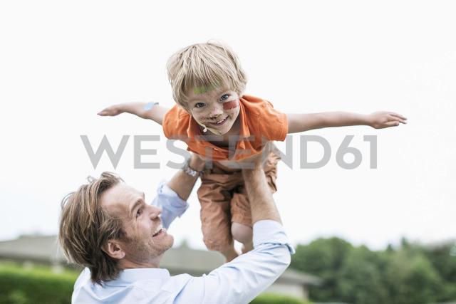 Playful father lifting injured son against clear sky - MASF04828 - Maskot ./Westend61