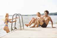 Playful friends on boardwalk at lake - MASF04831