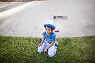 High angle view of boy sitting on grassy field - CAVF41953
