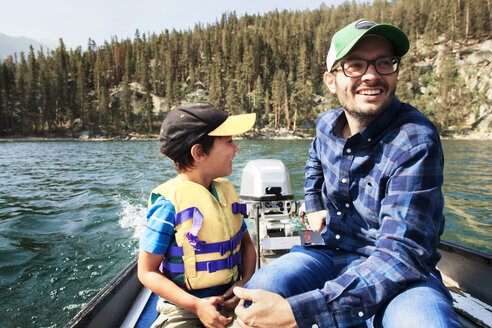 Happy father and son traveling in motorboat on lake - CAVF42019
