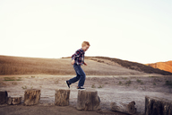 Side view of boy walking over woods at field against clear sky - CAVF42091