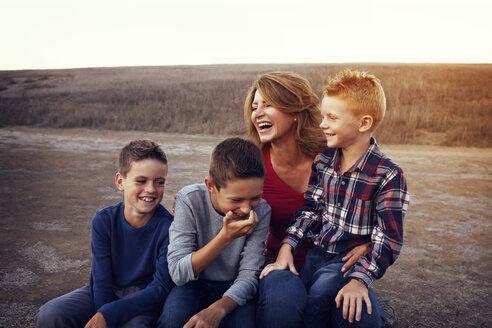 Happy family enjoying on field against clear sky - CAVF42094