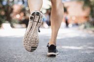 Low section of woman in sports shoes running on park street - MASF04855