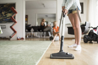 Low section of girl cleaning floor with vacuum cleaner at home - MASF04858