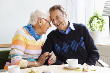 Loving senior couple laughing at nursing home - MASF04861