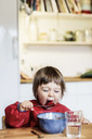 Little girl eating fruit salad at table in house - MASF04879