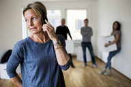Mature woman using mobile phone while family carrying moving boxes in background at home - MASF04894