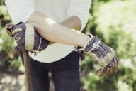 Midsection of man wearing gardening gloves at yard - MASF04900
